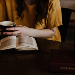 woman holding mug in front of book